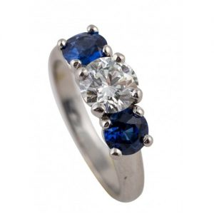 PLATINUM DIAMOND AND SAPPHIRE THREE-STONE ENGAGEMENT RING